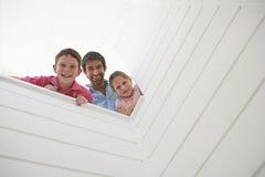 Fader With Children Looking över den vita väggen royaltyfria bilder