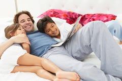 Fader And Children Relaxing i säng tillsammans royaltyfri bild