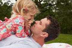 Fader With Daughter Relaxing på campa ferie royaltyfri bild