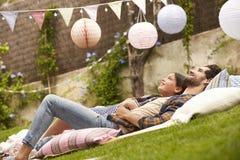 Fader With Daughter Relaxing på filten i trädgård tillsammans arkivfoton