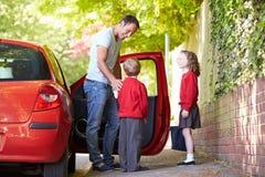Fader Driving To School med barn arkivfoto