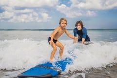 Fader eller instruktör som undervisar hans 4 den åriga sonen hur man surfar in royaltyfri foto