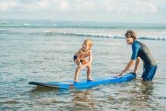 Fader eller instruktör som undervisar hans 4 den åriga sonen hur man surfar i havet på semester eller ferie Lopp och sportar med arkivbild