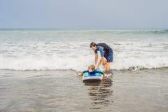 Fader eller instruktör som undervisar hans 5 den åriga sonen hur man surfar i havet på semester eller ferie Lopp och sportar med royaltyfri foto