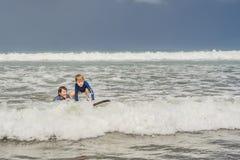 Fader eller instruktör som undervisar hans 5 den åriga sonen hur man surfar i havet på semester eller ferie Lopp och sportar med arkivfoto