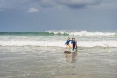 Fader eller instruktör som undervisar hans 5 den åriga sonen hur man surfar i havet på semester eller ferie Lopp och sportar med royaltyfria foton