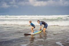 Fader eller instruktör som undervisar hans 5 den åriga sonen hur man surfar i havet på semester eller ferie Lopp och sportar med royaltyfri bild
