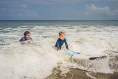 Fader eller instruktör som undervisar hans 5 den åriga sonen hur man surfar i havet på semester eller ferie Lopp och sportar med fotografering för bildbyråer