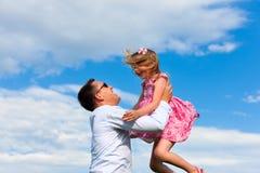 fader för angelägenhetdotterfamilj som leker su Arkivfoto