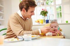 Fader Feeding Baby Sitting i hög stol på mattiden arkivbild