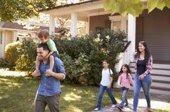 Fader Gives Son Ride på skuldror som hus för familjtjänstledigheter royaltyfri fotografi