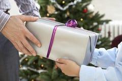 Fader Giving Christmas Present till sonen Arkivbilder