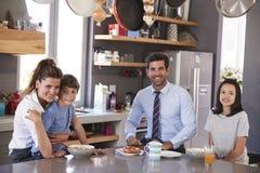 Fader Having Family Breakfast i kök, innan att lämna för arbete Fotografering för Bildbyråer