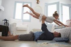 Fader Lifting Daughter Into luften inomhus royaltyfri fotografi