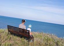 Fader med barnet som framme ser till havet av den härliga hav- och himmelsikten Arkivbild