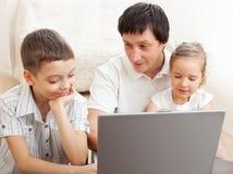 Fader med barnlek i datoren Royaltyfri Bild