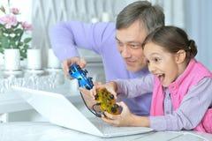 Fader med den lilla dottern som spelar dataspelen arkivbilder