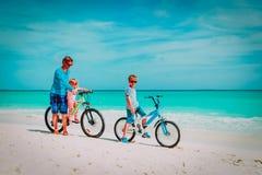 Fader med den lilla sonen och dottern som cyklar på stranden royaltyfria bilder