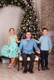 Fader med dottern och sonen i elegant kläder på julhelgdagsafton nära trädet för nytt år hemma som poserar arkivbilder