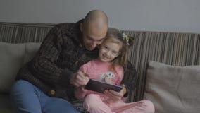 Fader med dottern som använder minnestavladatoren stock video