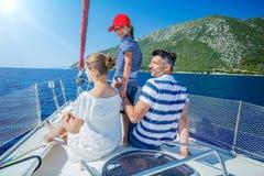 Fader med förtjusande ungar som vilar på yachten Royaltyfri Foto