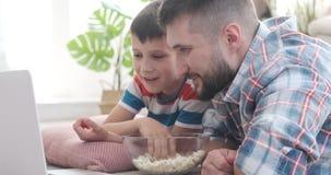 Fader med hållande ögonen på film för son hemma lager videofilmer