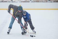Fader med hans son som spelar hockey Arkivbild