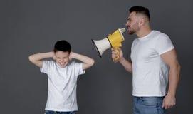 Fader med megafonen som skriker på stängande öron för son royaltyfri fotografi