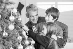 Fader med sonen och dottern som dekorerar julgranen Familj C Royaltyfri Fotografi