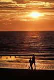 Fader med sonen på solnedgånghavet arkivbild
