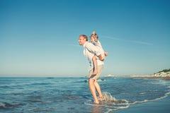 Fader med sonen som tillsammans spelar på havsbränninglinje Fotografering för Bildbyråer