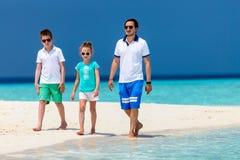 Fader med ungar på stranden Arkivbild