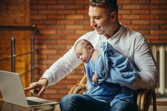 Fader With Newborn Baby som hemifrån arbetar genom att använda bärbara datorn royaltyfri bild