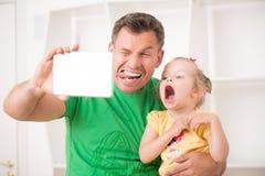 Fader och barn som hemma använder den elektroniska minnestavlan Royaltyfri Foto
