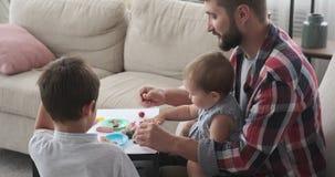 Fader och barn som spelar med färgplasticine arkivfilmer