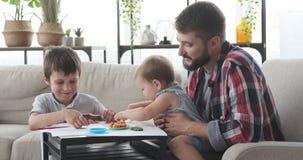 Fader och barn som spelar med plasticine arkivfilmer