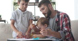 Fader och barn som spelar med plasticine stock video