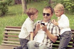 Fader och barn som spelar på parkera Royaltyfri Fotografi