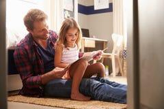 Fader och barndotter som tillsammans läser arkivfoto