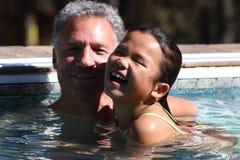 Fader och dotter i pölen Royaltyfri Foto
