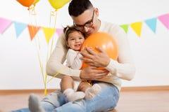 Fader och dotter med ballonger för födelsedagparti royaltyfria foton
