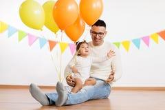 Fader och dotter med ballonger för födelsedagparti arkivfoton