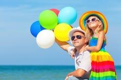 Fader och dotter med ballonger som spelar på stranden Royaltyfria Foton