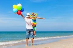 Fader och dotter med ballonger som spelar på stranden Arkivbilder