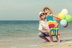 Fader och dotter med ballonger som spelar på stranden på daen Arkivbilder