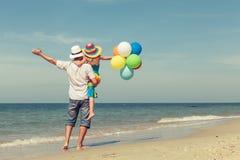 Fader och dotter med ballonger som spelar på stranden på daen Royaltyfri Bild