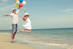 Fader och dotter med ballonger som spelar på stranden på daen Royaltyfri Foto
