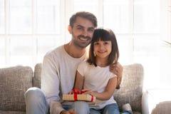 Fader och dotter med gåvaasken som sitter på soffan royaltyfri bild