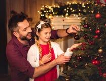 Fader och dotter som dekorerar julträdet fotografering för bildbyråer