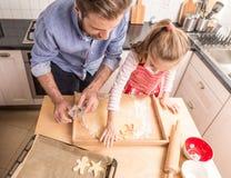 Fader och dotter som förbereder kakor för att baka i köket Arkivfoto